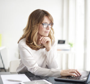 Woman with glasses wearing a white sweater looking at her computer in her home office.