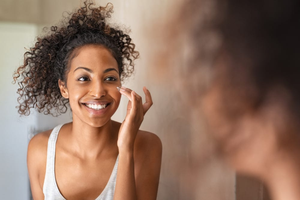 Woman applying face cream in the mirror. Med spa treatment for uneven skin tone.